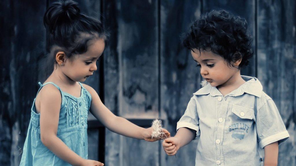 Kinder beschenken sich mit Blumen.