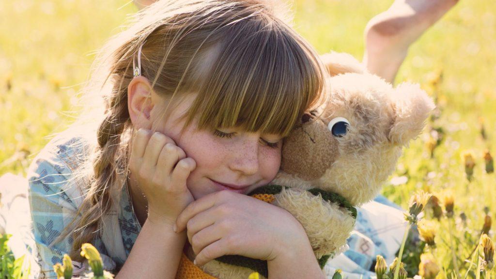 Glückliches Kind mit Teddy