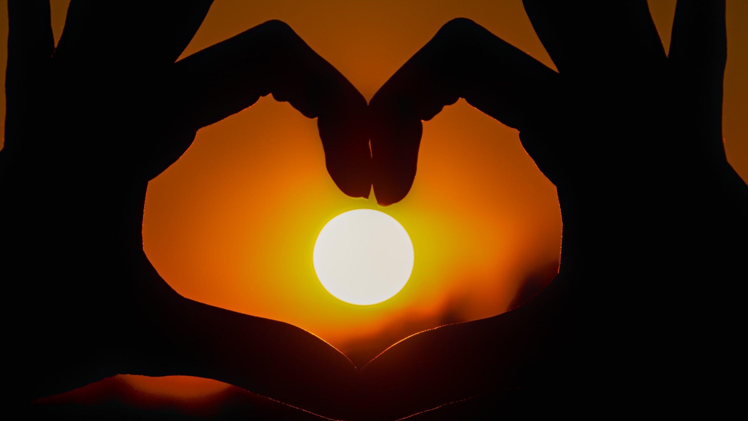 Hand macht Herz mit Sonne im Zentrum