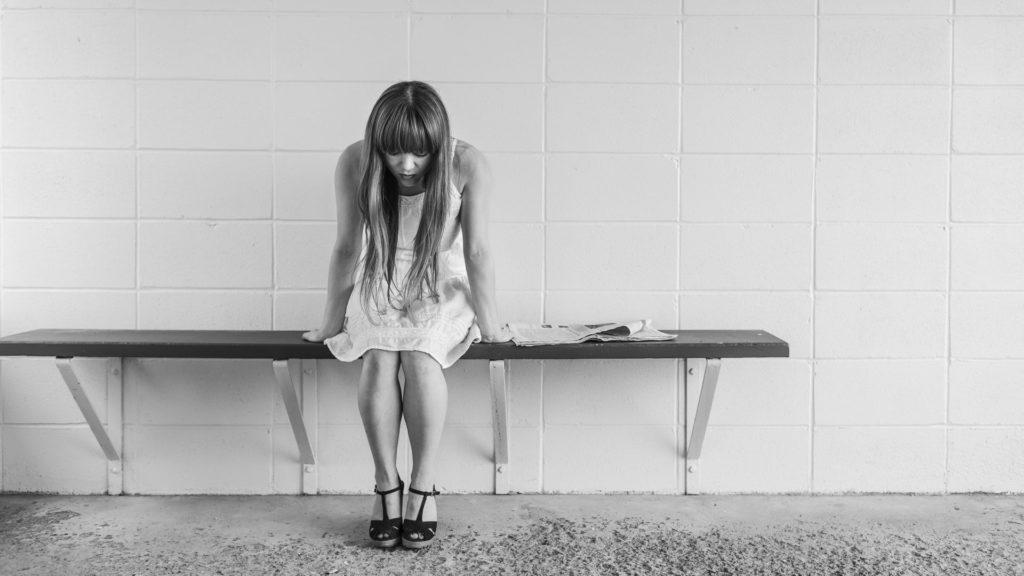 Traurige Frau auf Sitzbank